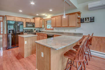 Kitchen with Counter, High Chairs, Refrigerator, Microwave, and A/C.