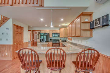 Kitchen with Counter, High Chairs, Refrigerator, and Microwave.