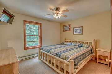 Bedroom with a Large Bed, Drawer Chest, Nightstand, and TV.