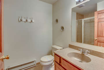 Sink, Mirror, and Toilet of the Bathroom with Shower.