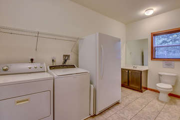 Laundry Room with Washer, Dryer, Refrigerator, Toilet, and Bathroom Sink.