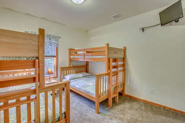 Bedroom with Two Bunk-Beds, Nightstand, and TV.