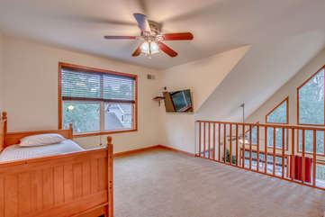Upstairs Room with One Bed, Ceiling Fan, and TV.
