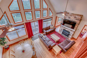 Great Room with Floor to Ceiling Windows, Fireplace, TV, Couches, and Dining Area.