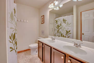 Double Sink Vanity, Big Mirror, Toilet, and Shower Curtain.