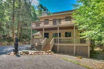 The exterior of this Lake Harmony rental, with its two patios and a bear statue out front.