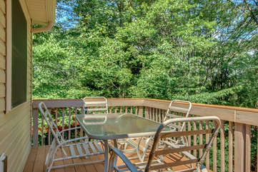 The upper balcony of this Lake Harmony rental, with a glass table and 4 outdoor chairs.