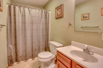A picture of the bathroom with the toilet, sink, and shower (with curtain closed) in shot.