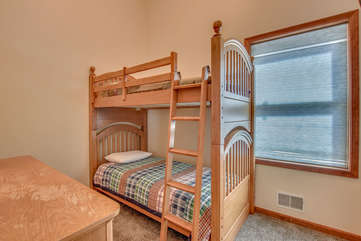 A bunkbed, with a dresser in the bottom left of the picture.