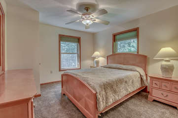 The bed in the master bedroom, with two nightstands on either side, and a vanity dresser at the foot of the bed.