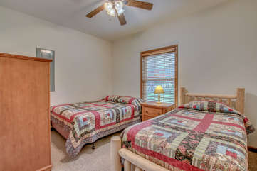 Bedroom with Two Beds, Nightstand, Table Lamp, Dresser, and Ceiling Fan.