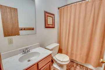 Bathroom with Shower Curtain, Sink, Mirror, and Toilet.