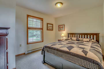 Bedroom with One Large Bed, Nightstand, Table Lamp, and Dresser.