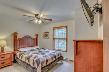 Bedroom with One Large Bed, Nightstand, Dresser, TV, and Ceiling Fan.