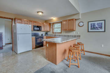 Kitchen with Counter, Stools, and Refrigerator, and Microwave.