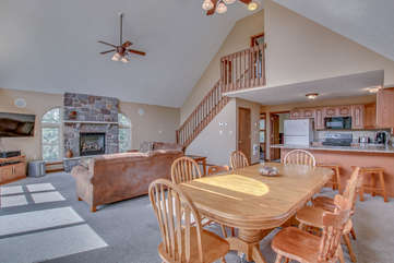 Kitchen, Dining Table, Chairs, Couch, Fireplace, TV, Ceiling Fans, and Stairs.