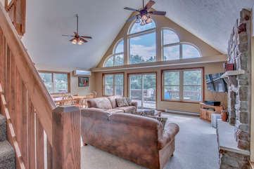 Couches, Fireplace, TV, Dining Table, Windows, Sliding Door, and Ceiling Fans.