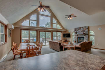 Great Room with Dining Table, Chairs, Couches, Fireplace, TV, and Ceiling Fans.