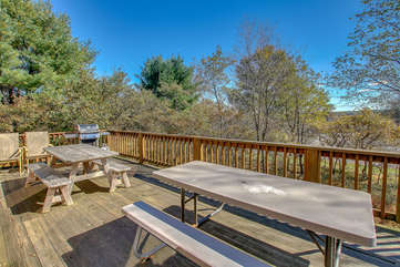 Three Large Picnic Tables Featured on Wood Deck.