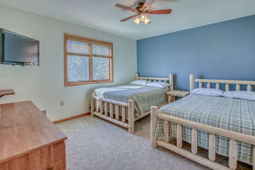 An Image of Bedroom with Two Beds, a Dresser, and TV.