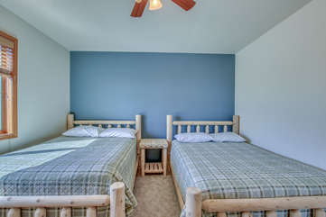 Two Wooden Beds Featured in Bedroom with Dark Blue Accent Wall.