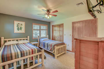 Two Beds, a Dresser, and TV on Wall in Bedroom.