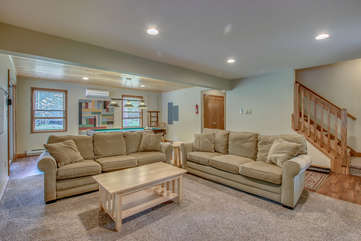 basement room with two couches and a coffee