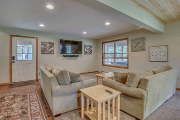 basement room with two couches and a TV
