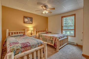 tan bedroom with two beds beneath ceiling fan