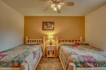 two beds in tan bedroom beneath ceiling fan