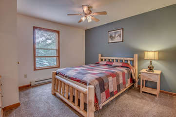 single bed in blue bedroom with nearby ceiling fan
