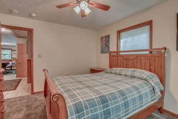 A picture of a bed in the center of a bedroom, with a door open to the game room of this Lake Harmony rental.