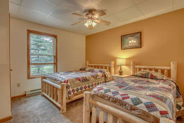 tan bedroom with two beds and nearby windows