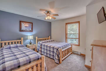 blue bedroom with two beds and ceiling fan