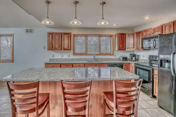 Spacious Kitchen Features Island, Chairs, and Refrigerator.