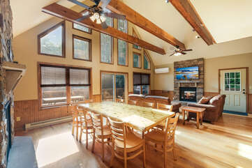 Great room with arched ceiling, large windows, dining table with chairs, couches, TV and fireplace.