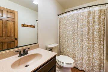 Toilet, sink, and shower of bathroom, with curtain closed and door visible in the sink mirror.