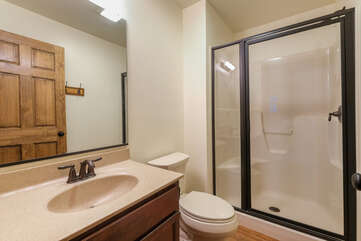 Bathroom with toilet, sink and mirror, and walk in shower with glass door,