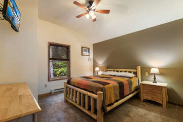 Large bed, nightstands, dresser, and TV of a room in this luxurious Poconos vacation rental.