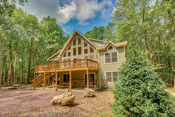 Angled photo of the exterior of this luxurious Poconos vacation rental, with view of elevated porch.