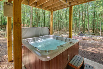 The outdoor hot tub of this luxurious Poconos vacation rental, filled with water and powered on.