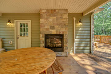 The picnic table and outdoor fireplace located on the porch.
