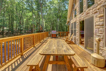 Picnic table and grill on the porch of this luxurious Poconos vacation rental.