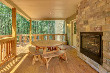 The outdoor fireplace located on the porch, next to a round picnic table.