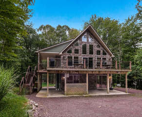 The exterior view and deck of a Pocono Getaway Rental