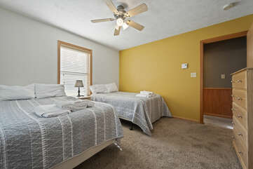 Ceiling fan in bedroom with two beds beneath.