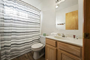 Bathroom area with tub/shower combo.