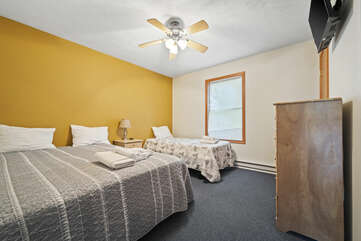 Bedroom with two beds and nearby ceiling fan.