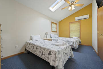 Two bed bedroom with ceiling fan.