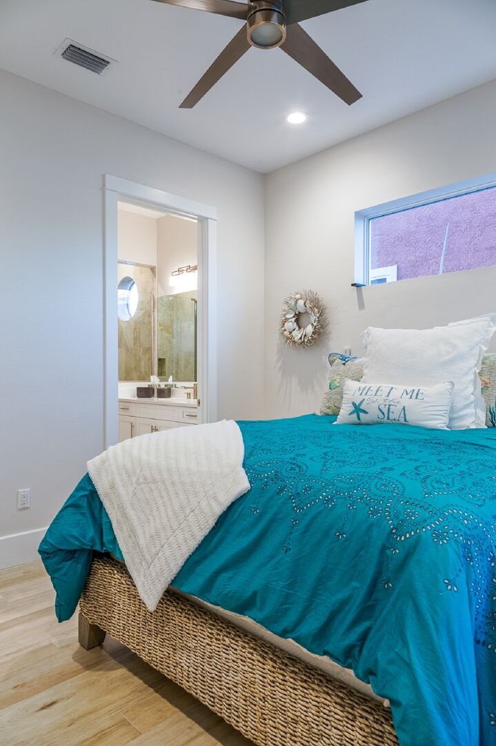 Large bed with blue sheets, in front of a doorway to a private bathroom.